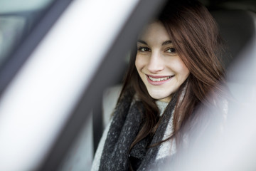 Portrait of smiling young woman driving car in winter
