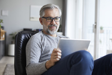 Portrait of mature man using tablet at home