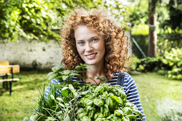 Portrait of young woman with fresh herbs in garden