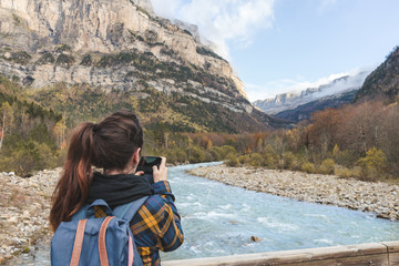 Spain, Ordesa y Monte Perdido National Park, back view of woman with backpack taking photo