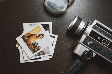 Stack of instant photos of young woman next to camera