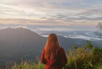 Cute girl hiking adventure on the high mountain with beautiful views of mist. at Doi Phu Kha in Nan.