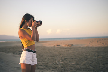 Teenage girl taking photos with camera on the beach at sunset