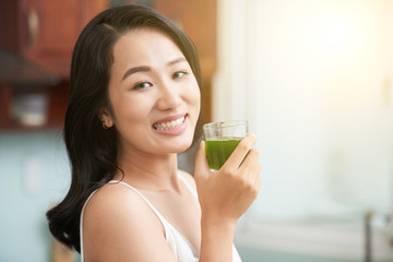 Smiling Asian woman holding glass with fresh green juice being healthy and smiling at camera