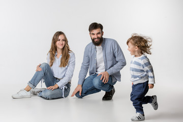 A happy smiling family on white studio background. The father, mother and son posing together