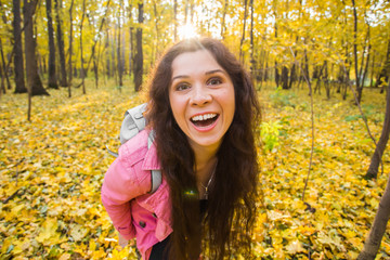 April fools day concept - portrait of funny smiling woman in autumn forest