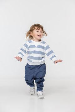 Portrait of happy joyful running beautiful little boy, studio shot on white