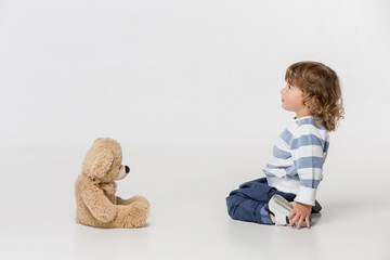 Portrait of happy joyful beautiful little boy playing with teddy bear toy , studio shot on white