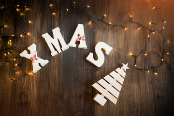 Christmas card with wooden letters and pine in light beams and garlands on grunge wooden surface top view