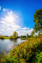 Wall Mural - Landscape in summer with river, trees and meadows in bright sunshine