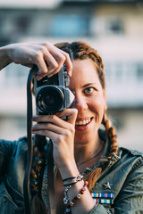 Pretty redhead girl with braids taking pictures.