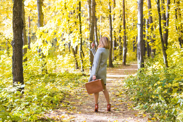 Season, technology and people concept - beautiful young woman in autumn nature taking selfie with smartphone