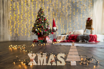 Wooden letters Xmas on the christmas tree background