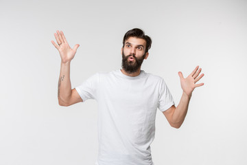 Wow. Attractive male half-length front portrait on white studio backgroud. Young emotional surprised bearded man standing with open mouth. Human emotions, facial expression concept. Trendy colors