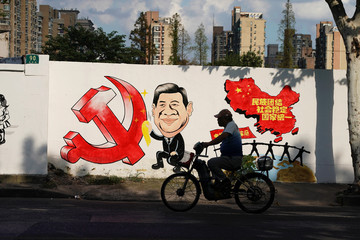 A man rides a bicycle next to a mural showing an image of Chinese President Xi Jinping along a street in Shanghai