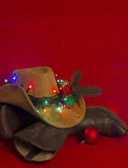 Cowboy Christmas.American West traditional boots on christmas red background