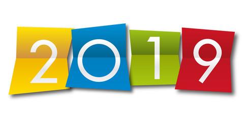 Carte de vœux 2019 avec l'année inscrite sur quatre papiers pliés de couleurs différentes, un jaune, un bleu, un rouge et un vert