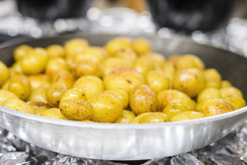 Many small potatoes on silver frying pan