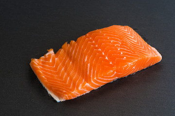 Fresh raw salmon filet on black background