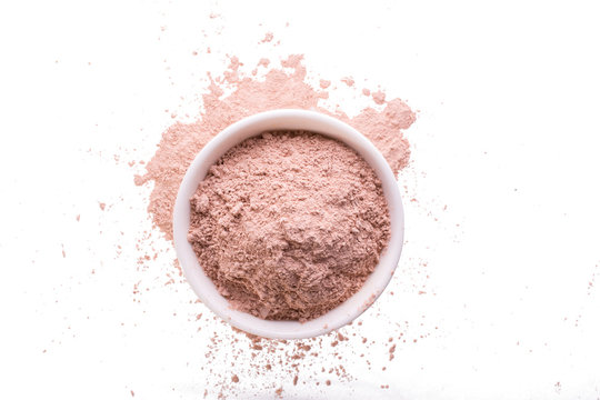 Dry pink clay powder mask for face and body  in ceramic bowl isolated on white