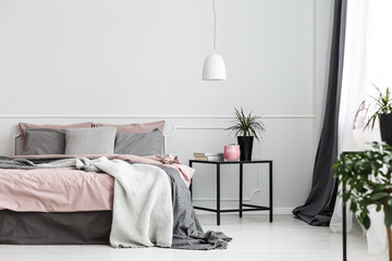 Warm blankets and gray pillows on a cozy double bed with dirty pink sheets by an empty wall of a white bedroom interior