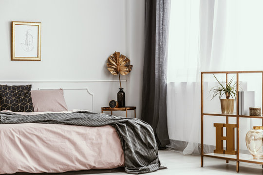 Framed silhouette drawing on a white wall of a feminine and artistic bedroom interior with golden decor and pink sheets