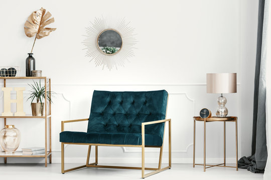 Golden decorations and furniture in an expensive living room interior with an emerald green sofa by a white wall with molding