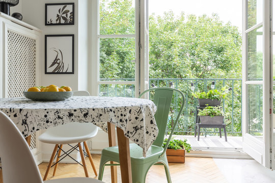 Real photo of a scandi dining room interior with a patterned cloth on a table, chairs and balcony in the background