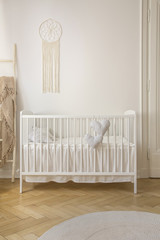 Two heart shaped pillows placed on baby crib standing in white room interior with macrame on wall and herringbone parquet in the real photo