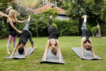 Group of young women practising one-legged downward facing dog pose under control of female yoga teacher outdoors