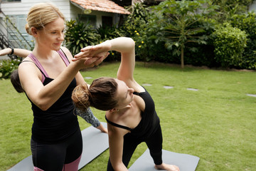 Professional attractive female yoga teacher correcting pose of young Caucasian  woman doing yoga outdoors