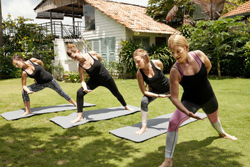 Group of young Caucasian women in sportswear doing yoga with professional yoga instructor on sunny morning outdoors