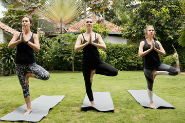 Young Caucasian women in activewear standing on yoga mats and balancing in tree yoga pose outdoors