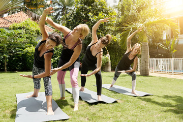 Qualified female yoga instructor correcting poses of young women practising yoga on beautiful sunny morning outdoors