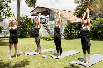 Young Caucasian women doing sun salutation exercises while practising yoga with professional female teacher outdoors