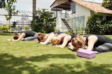 Group of young women in activewear stretching on mats and relaxing while having yoga practice on sunny morning outdoors
