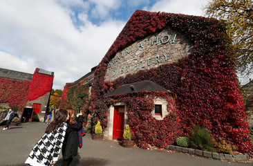 Tourists photograph autumn foliage on the Blair Athol distillery in Pitlochry, Scotland