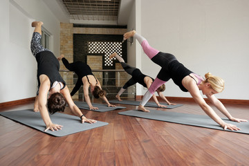 Group of young Caucasian women standing in one-legged downward-facing dog pose while doing yoga with qualified instructor indoors
