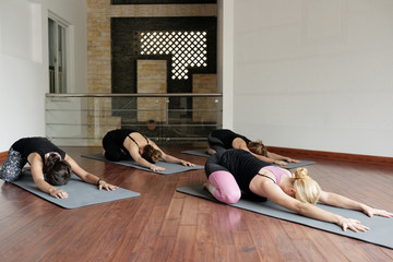 Group of young Caucasian females relaxing in child pose while having yoga class with professional female instructor in studio