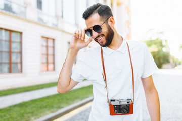 Stylish hipster with a beard and a camera, walking around the city with a camera