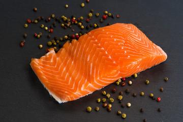 Fresh salmon filet on black cutting board with pepper