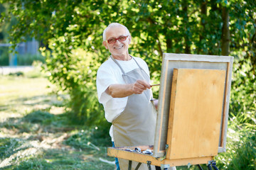 Senior male artist drawing picture at park using palette with paints.