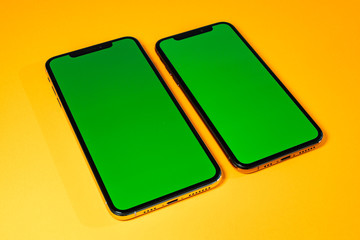 Green chroma key on on new mobile smartphne as hero object on bright glamorous modern neon pop orange background - smartphone ready to insert your app