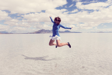 A woman jumps at the Bonneville Salt flats when the salt flats are flooded in the spring.. Instagram style filter applied for artistic effect