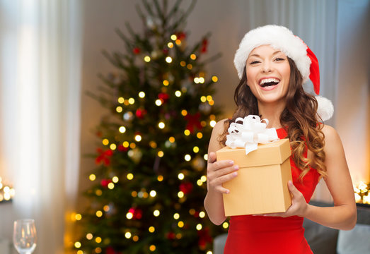 holidays and people concept - smiling woman in santa hat with gift box over living room and christmas tree background