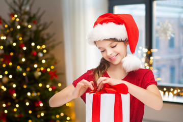 holidays and childhood concept - happy girl with gift box at home over room with christmas tree background