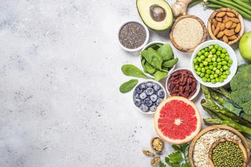 Superfoods on light stone background. Healthy vegan food.