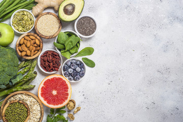Superfoods on light stone background. Healthy vegan food.