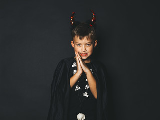 little boy with red halloween horns and black cape in front of black background