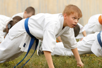 Boy teenager in kimono performs push-ups on fists
